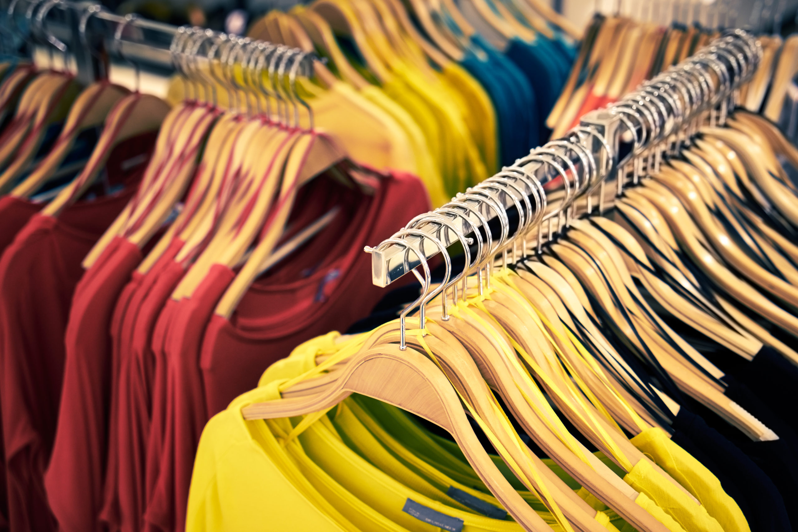 iew of clothes shop with t-shirts hanging on stand